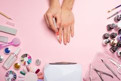 Nail care. beautiful women hands making nails painted with pink gentle nail polish on a pink background. Women's hands near a set royalty free stock photography