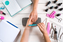 Nail care. Closeup of female hands filing nails with professional nail file in beauty nail salon. Top view Royalty Free Stock Photo