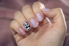 The nail is decorated with a picture of a charming panda Stock Photos