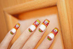 Nail design. Nail design is completely made using colored acrylics on orange wooden background stock image
