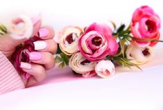 Nail design manicure decorated with flowers. Nail design pink color. Manicured hand with flowers on table with empty copy space stock photo