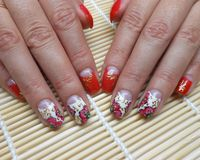 Nail design: red flowers. With gold swirls on a white background royalty free stock image