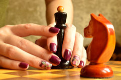 Nail designs: dark plum gloss and Matt flower. Queen vs. knight. Female fingers with bright nail designs hold the chess piece. Black Queen and purple manicure stock photography