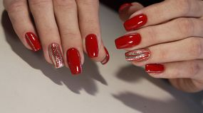 Nail designs with different sequins in the shape of hearts on red and pink nails for stock photos