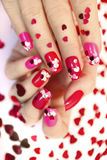 Nail designs with hearts. Nail designs with different sequins in the shape of hearts on red and pink nails for girls royalty free stock photos
