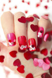Nail designs with hearts. Nail designs with different sequins in the shape of hearts on red and pink nails for girls Stock Photo