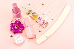 Nail designs on tips and manicure set. On a pink background stock photography