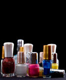 Nail enamel. Multicolored cosmetics bottles with nail enamel over black with copyspace royalty free stock photography