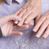 Nail Extensions. Older senior womans hand receiving home spa/beauty treatment of nail extensions Stock Photography