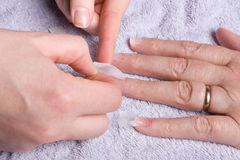 Nail Extensions. Older senior womans hand recieving home spa/beauty treatment of nail extensions Stock Images