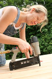 Nail Gun. An attractive girl shows off her handywoman skills by nailing on new cedar decking Stock Photography