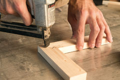 Nail gun. Joinery uses a nail gun to attach pieces of wood royalty free stock images