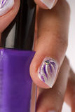 Nail lacquer. Beautifully decorated hand holding a bottle of nail lacquer Stock Image