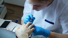 Nail master applies firming nail polish on nails in beauty salon, close-up.  stock photography