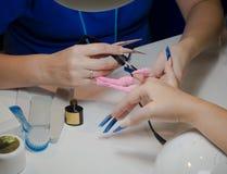 Nail master apply gel polish shellac on a woman hand finger nail stilettos. Nail master apply gel polish shellac on a woman hand finger nail stilettos royalty free stock photos