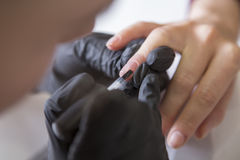 Nail master in rubber gloves make manicure care cuticle on a w. Oman hand finger nail. Healthcare beauty cosmetic spa procedure in a salon Royalty Free Stock Image