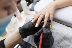 Nail master wearing a mask and black gloves applying brush on acrylic nails in the salon. Closeup. Closeup on nail master wearing a mask and black gloves royalty free stock images