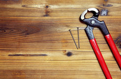 Nail and nail puller on a wood board Royalty Free Stock Images