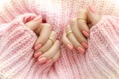 Nail Polish. Art Manicure. Modern style pink Nail Polish.Stylish pastel Color pink Nails holding wool material sleeve royalty free stock photo