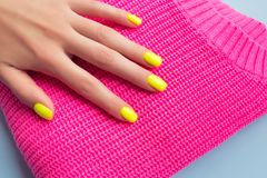 Stylish trendy female manicure. Neon yellow nails on plastic pink background stock photos