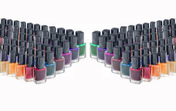 Nail polish for beauty salons. It is a lot of glass bottles with nail polishes isolated on white background. Multi-colored bright colors of nail polishes with stock image