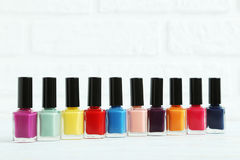 Nail polish. Bottles of nail polish on brick wall background Royalty Free Stock Photos