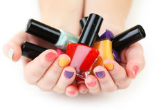 Nail polish bottles. Colorful nail polish bottles in woman hands royalty free stock images