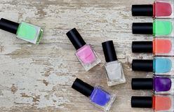 Nail polish bottles of different colors on white wooden table. Nail polish bottles of different colors on rustic white wooden table royalty free stock photo