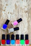 Nail polish bottles of different colors on white wooden table. Nail polish bottles of different colors on rustic white wooden table royalty free stock image