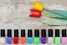 Nail polish bottles of different colors on white wooden table. Nail polish bottles of different colors on rustic white wooden table stock photography