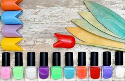 Nail polish bottles of different colors on white wooden table. Nail polish bottles of different colors on rustic white wooden table stock photo