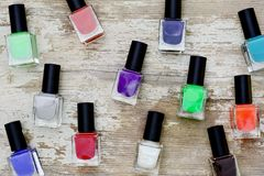Nail polish bottles of different colors on white wooden table. Nail polish bottles of different colors on rustic white wooden table stock image