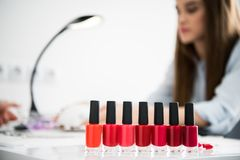 Nail polish bottles with shades of red. Standing on workplace in beauty salon Royalty Free Stock Images