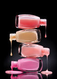 Nail polish dripping from open bottles on black background. Stock Photo