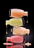 Nail polish dripping from open glass bottles on black background. Close up Stock Images