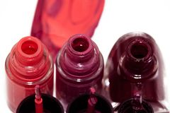 nail polish dripping from stacked bottles on white background stock image