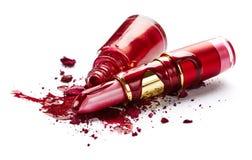 Nail polish, eye shadow and lipstick. Red nail polish, crushed eye shadow and lipstick isolated on white background royalty free stock image