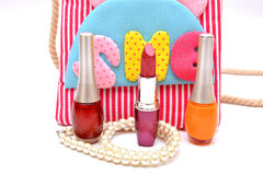 Nail polish and lip gloss isolated on white with girl handbag Royalty Free Stock Image