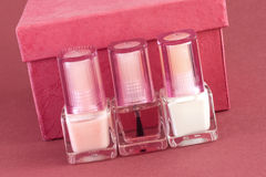 Nail polish and red box 2. Three bottles of nail polish for French manicure and red box on red background Stock Photos
