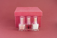 Nail polish and red box 3. Three bottles of nail polish for French manicure and red box on red background Stock Image