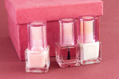 Nail polish and red box 4. Three bottles of nail polish for French manicure and red box on red background Royalty Free Stock Photography