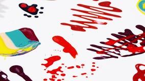 Nail polish (varnish) mixed multicolor blots rotating over white stock video footage