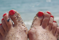 Nail polish on your toes at the beach with sand and shells on th Stock Photo