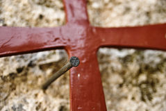 Nail and red cross Stock Photography