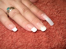 Nail repair. White female right hand fingers with french manicure getting the broken nail of the forefinger fixed Royalty Free Stock Photography