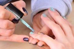 Nail salon - Applying green nail polish on female fingers. Royalty Free Stock Photo