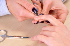 Nail salon - Cut cuticle on the women forefinger Royalty Free Stock Photography
