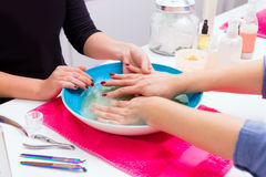 Nail saloon scrub bath exfoliant hands in bowl water Stock Photography