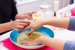 Nail saloon scrub bath exfoliant hands in bowl water Stock Photos
