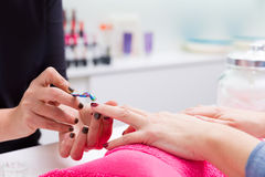 Nail saloon woman with hand manicure cuticle scraper pusher Royalty Free Stock Photos